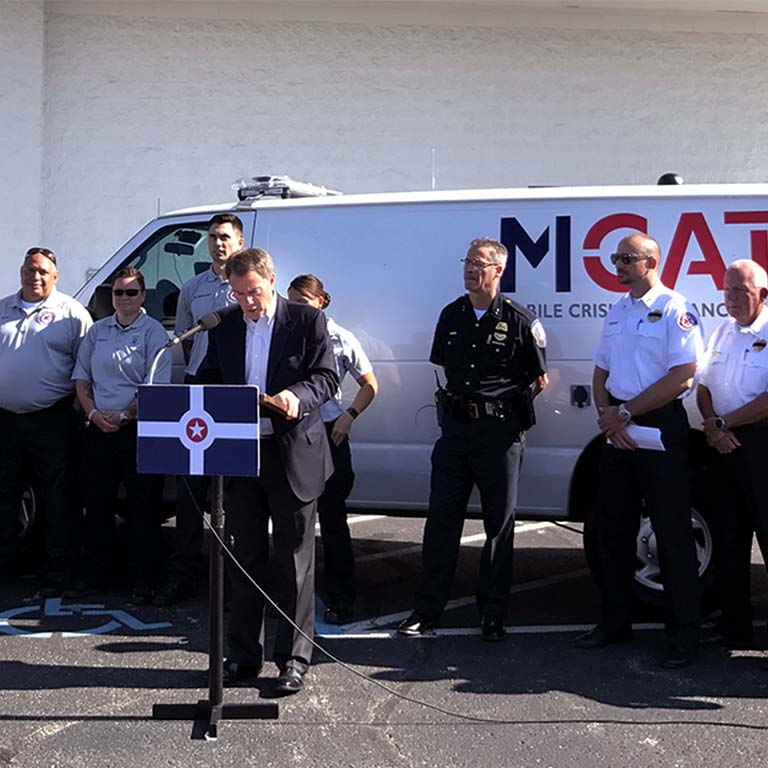 Indianapolis Mayor Joe Hogsett speaks while public safety workers stand by an MCAT van.