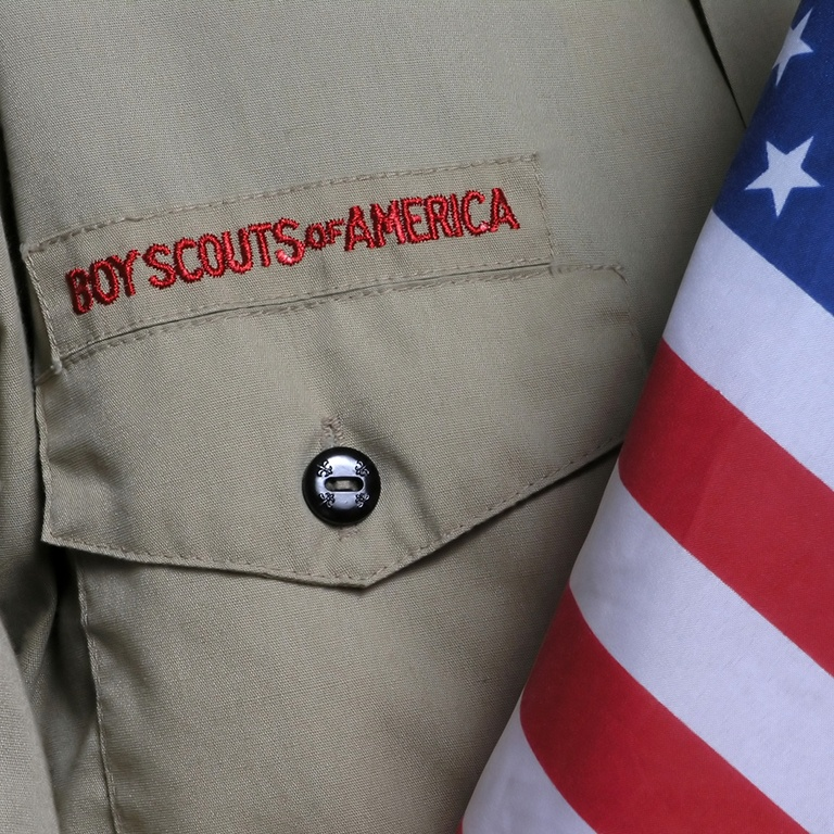 A close-up of a buttoned shirt pocket with 'Boy Scouts of America' embroidered above it